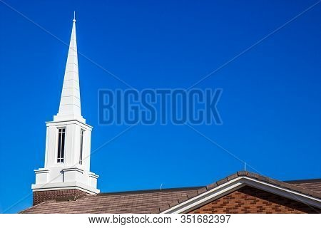 White Steeple With Windows Atop A Neighborhood Church