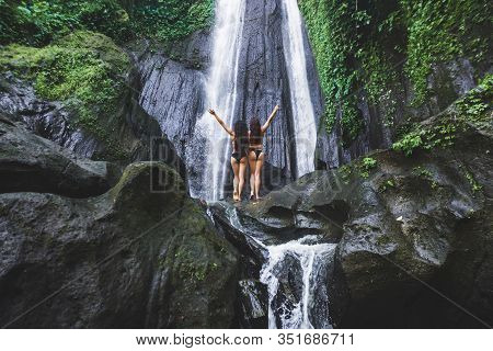 Two Slim Women Relaxing Near Beautiful Waterfall In Bali Jungle. Nature Adventure Dusun Kuning In Ub
