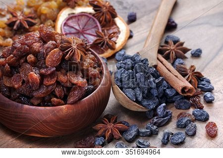 Raisins In A Bowl On A Wooden Table. Black And Red Raisins, Cinnamon And Anise Stars Close Up