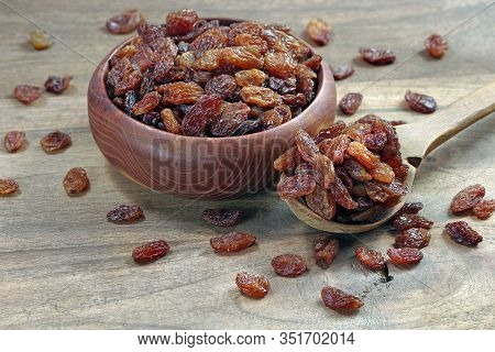 Raisins In A Bowl On A Wooden Table. Raisins In A Spoon