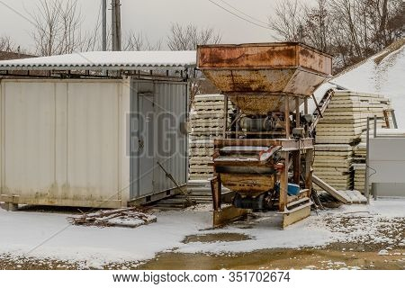 Feed Chute And Conveyer Belt Next To Metal Building In Snow Covered Rural Construction Site.