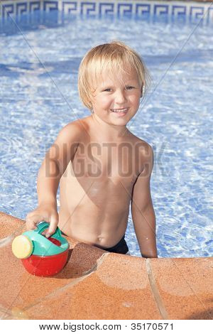 Boy With Watering Can In The Swimming Pool