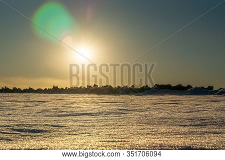 Arctic Lifeless Landscape With Hummocks On The Horizon, Low Sun Casts Lens Flare
