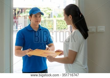 Asian Delivery Young Man In Blue Uniform Smile And Holding Letter Or Document Envelope In Front Hous