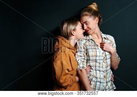 Portrait Of Young Gay Couple, Lesbian Women Hugging On Black Background With Copy Space. Сoncept Of