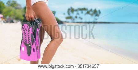 Snorkel fins girl going snorkeling swimming holding flippers equipment on beach panoramic background - pink scuba diving mask and fins icon for travel vacation concept.