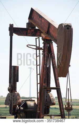 Oil well and windmill in Ayoluengo de la Lora, Burgo Province, Castilla Leon in Spain.