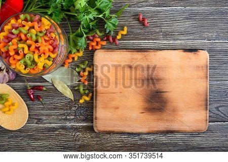 Cavatappi Colored Raw Pasta In A Glass Jar, Fresh Vegetables, Greens, Cutting Board On A Wooden Back