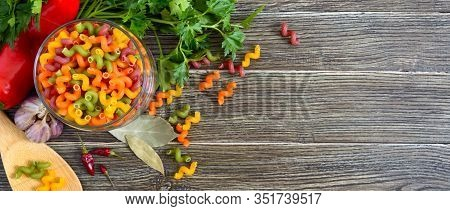 Cavatappi Colored Raw Pasta In A Glass Jar, Fresh Vegetables, Greens On A Wooden Background. Pasta C