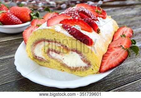Sweet Biscuit Roll With Strawberries And Cream On A Wooden Background.