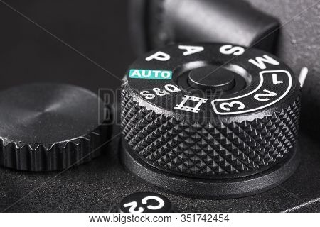 Black Switch Of The Shooting Mode On The Camera Close-up With White Letters And Numbers On A Blurred