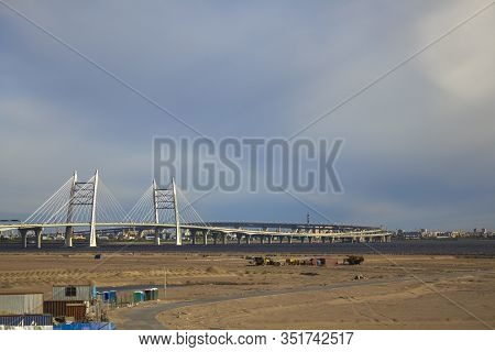 White Cable-stayed Bridge In The Sandy Desert Over The River Against The Backdrop Of The City Under