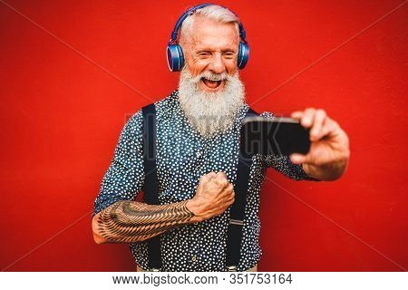 Senior Hipster Man Using Smartphone App For Creating Playlist With Music - Trendy Tattoo Guy Having