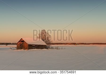The Winter Sun Rises And Colours The Snow Covered Landscape Beautifully At The Rural Finland. The Mi