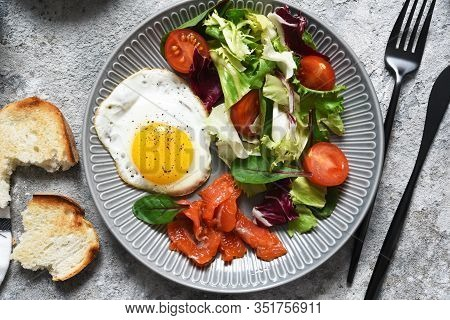 Classic Breakfast - Fried Eggs With Salad And Salmon With Fried Toast On The Kitchen Table.