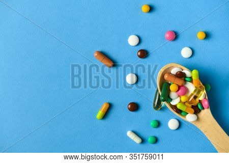 Wooden spoon full of pills, tablets, vitamins, drugs, omega 3 fish oil, gel capsules, medicament and food supplement for health care. Blue background.