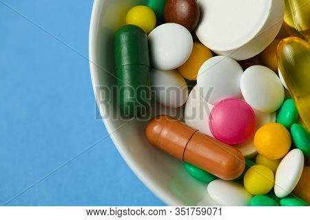 A dish full of pills, tablets, vitamins, drugs, omega 3 fish oil, gel capsules, medicament and food supplement for health care. Blue background.