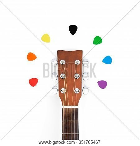 Colorful Picks Around Acoustic Guitars Headstock. Isolated Flat Lay