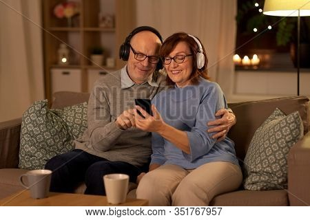 technology, old age and people concept - happy senior couple with smartphone and headphones at home in evening