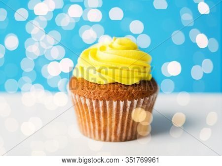 food, junk-food, culinary, baking and eating concept - close up of cupcake or muffin with yellow buttercream frosting over festive lights on blue background
