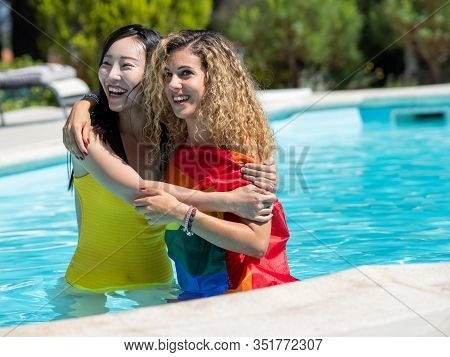 Stock Photo Of Two Girls Of Different Ethnicities In The Water Of A Swimming Pool Embraced With An L