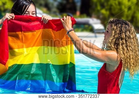 Stock Photo Of Two Girls Of Different Ethnicities In The Water Of A Swimming Pool With A Raised Lgtb