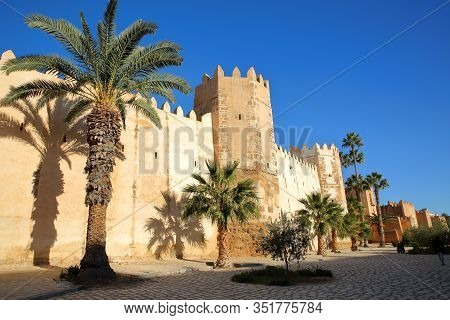 The Impressive Ramparts Of The Medina Surrounded By Colorful Palmtrees And A Large Cobbled Walkway I