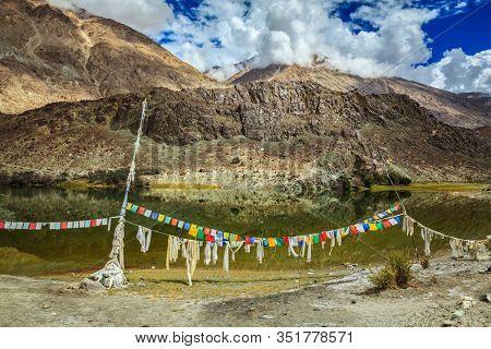 Lohan Tso mountain lake - sacred holy Tibetan buddhist buddhism piligrimage site with lungta prayer flags. Nubra valley, Ladakh, India