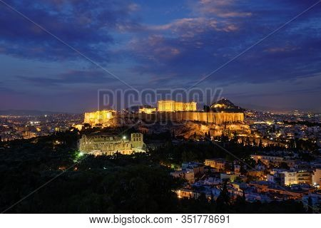 Parthenon Temple and Amphiteater are the antique iconic greek tourist landmark at the Acropolis of Athens and ancient European civilization architecture. View from Philopappos Hill at night. Greece