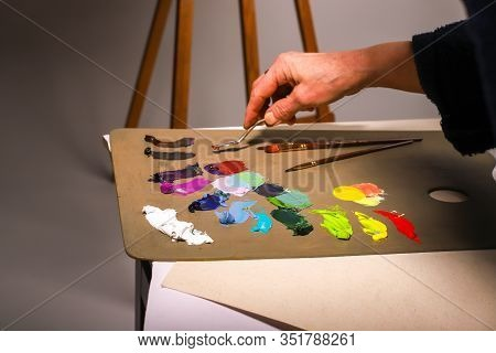 The Hand Of The Artist Works With Paints. The Artist Stirs Paints. The Female Hand Of An Elderly Art