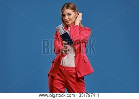 Blonde Lady In White Blouse And Red Pantsuit. She Is Tucking Her Hair, Holding Passport And Ticket W