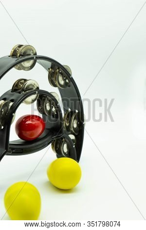 Black Tambourine With Coloured Egg Shakers On A White Background. Vertical Image. Concept Of Percuss