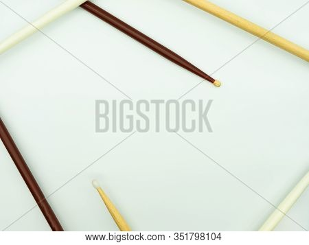 Top View Of Drumsticks On White Background Forming A Frame, With Space In The Middle Of The Image Fo