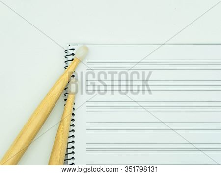 Top View Wooden Sticks On A Music Notebook With Staves. Concept Music.
