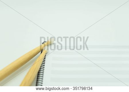 Close Up Wooden Sticks On A Music Notebook With Pentagram. Concept Music.