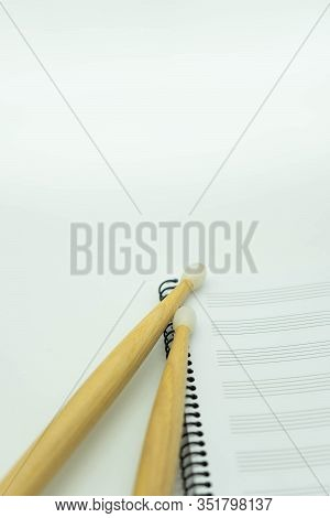 Vertical View Wooden Sticks On A Music Notebook With Pentagram. Concept Music.