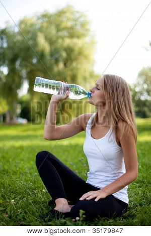 Beautiful Young Woman Sitting On Grass And Drinking Water