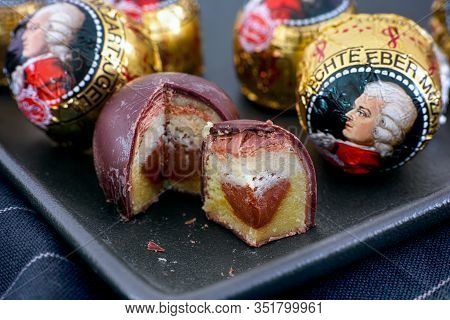 Tambov, Russian Federation - February 14, 2020 Mozart Candies On Black Plate.  One Candy Is Open And