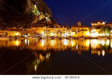Illuminated Pirate Castle and Town of Omis Reflecting in the Cetina River at Night Croatia poster