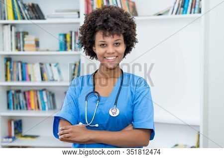 Portrait Of Laughing African American Nurse At Work At Hospital