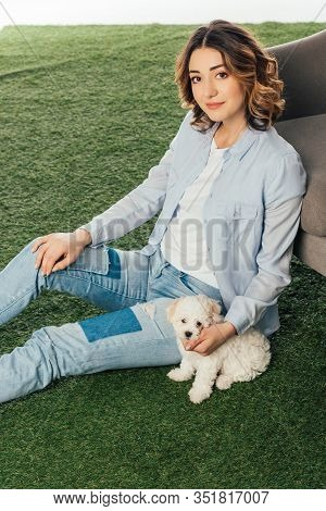 Smiling Woman With Cute Havanese Puppy Sitting On Grass