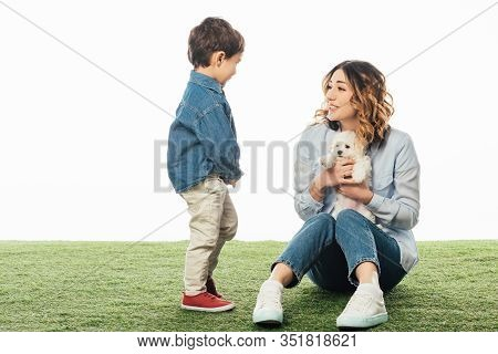 Smiling Mother Holding Havanese Puppy And Looking At Son Isolated On White