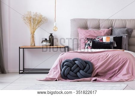 Knot Pillow Next To Elegant King Size Bed With Pastel Pink Bedding And Pillows
