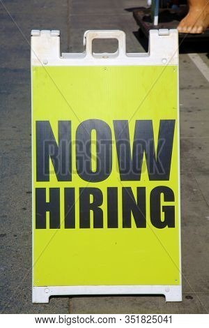 NOW HIRING. A Now Hiring A Frame Sign. Help Wanted. Now Hiring signboard. Looking for work. Looking for employees. Looking to hire. Job Offer. Yellow Sign.