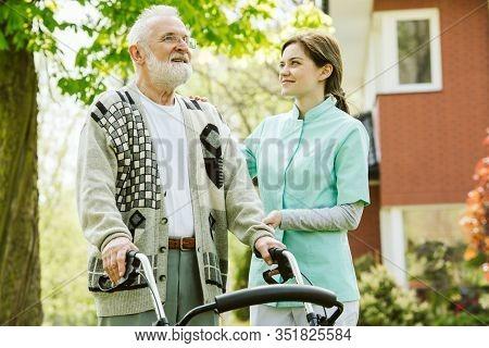 Senior Man With Walker During Walk In The Park Of Modern Nursing Home