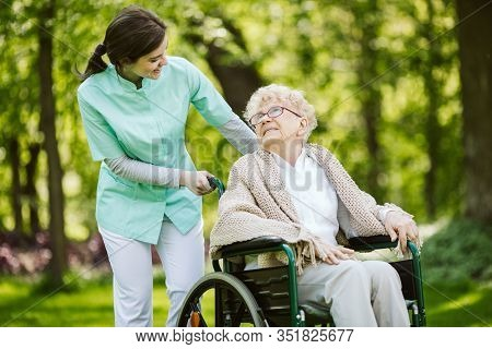 Happy Senior Woman And Helpful Caregiver, Nursing Home Concept Photos