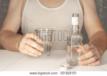 A Single Man, An Alcoholic Without A Face In A White T-shirt, Sits At A Table And Is About To Drink