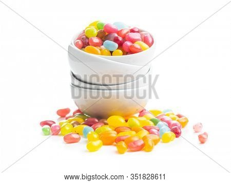 Fruity jellybeans. Tasty colorful jelly beans in bowl isolated on white background.