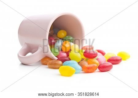 Fruity jellybeans. Tasty colorful jelly beans in cup isolated on white background.