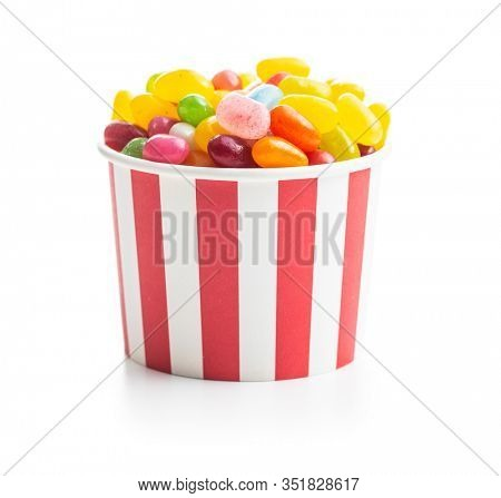 Fruity jellybeans. Tasty colorful jelly beans in paper cup isolated on white background.